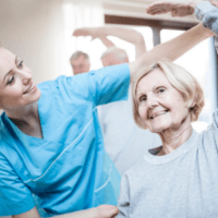 An elderly woman is assisted with personal exercise by her carer.