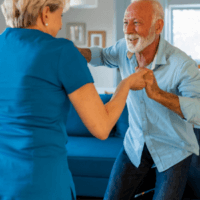 An elderly man dances with his care worker